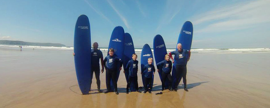 family surfing on saunton beach in devon